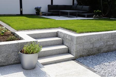 Jardín limpio y ordenado con paredes de granito y escalones de bloque macizo Foto de archivo