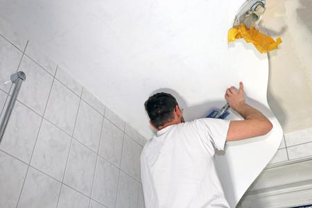 Wallpaper installer hanging wallpaper on the ceiling