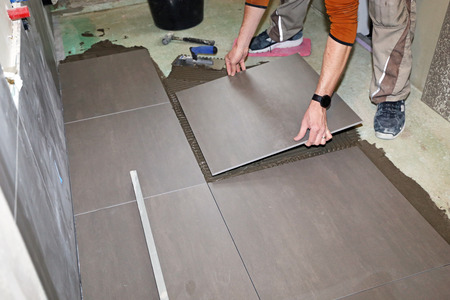 Worker laying floor tiles 免版税图像