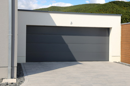 New black garage door with mountains and forest in the background Imagens