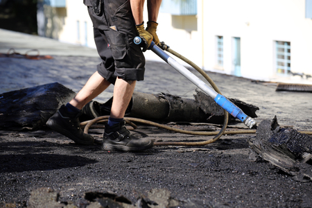 Roofers remove old bitumen and roof waterproofing