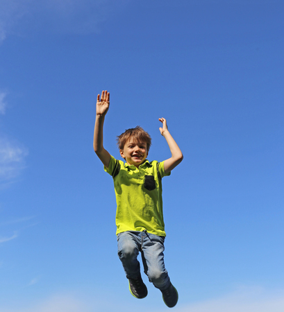 Boy jumps in the air, in the background blue sky