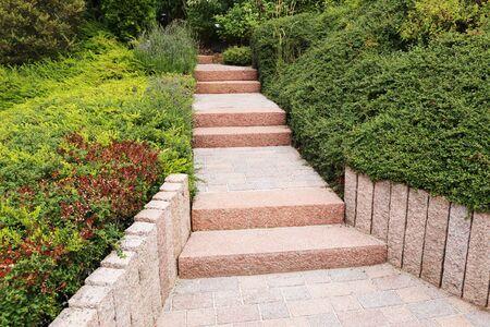 Giardino anteriore pulito e ordinato con gradini in blocchi solidi, ghiaia decorativa e piantagione
