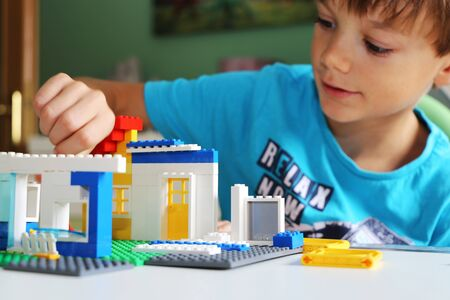 Boy builds a house with building blocks Imagens