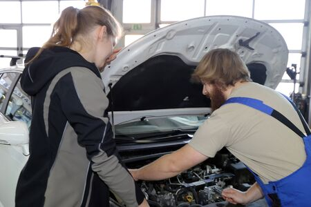 Car mechanic with a female customer