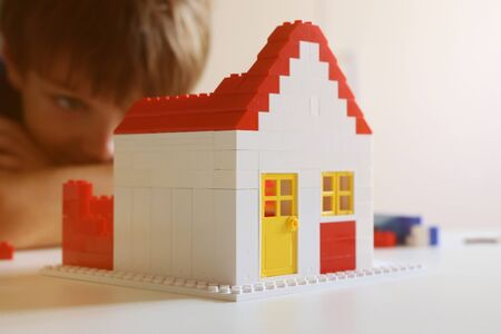 Boy builds a residential with building blocks