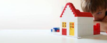 Junge baut ein Wohnhaus mit Bauklötzen