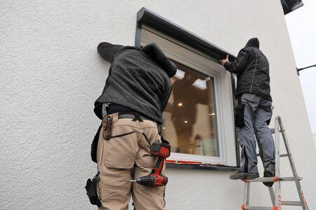 Worker installing a roller shutter 免版税图像