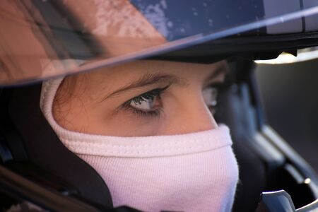 Female race car driver wears helmet and balaclava