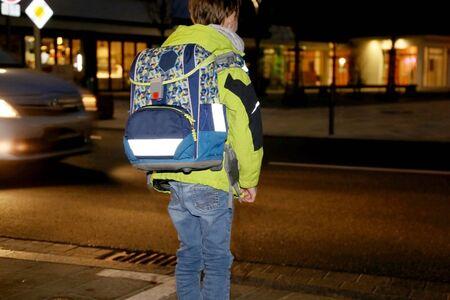 Schoolchild on the way to school after dark