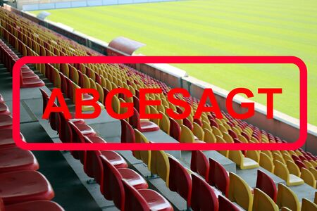 Red sign in german letters with the information canceled (event canceled) with empty stadium in the background
