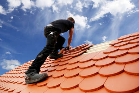Roofing work, new covering of a tiled roof Foto de archivo