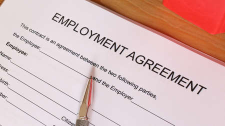 Symbol image: Blank form of an employment agreement on a desk Foto de archivo