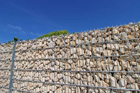 Close up of a gabion as a modern and high-quality visual protection and property boundary on a residential house Banco de Imagens