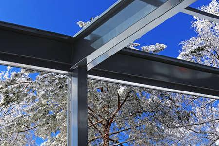 Interior view of a modern conservatory (winter garden) in an alpine winter landscape Standard-Bild