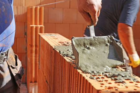 Construction worker (bricklayer) works on the construction site