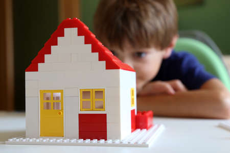 Symbol image: Boy builds a house with building blocks (Model released) Stock fotó