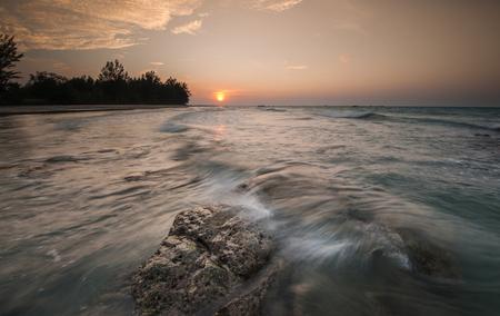orange sunset: orange sunset with waves trail as foreground Stock Photo