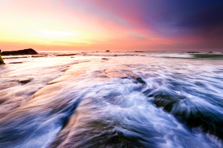 sunset seascape with rocks covered by green moss and waves trails. Photo taken at Kudat, Sabah Malaysia. 写真素材