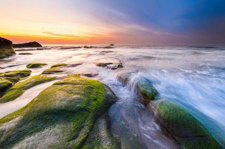 sunset seascape with rocks covered by green moss and waves trails. Photo taken at Kudat, Sabah Malaysia. Stock Photo