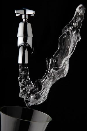 Water flowing upwards out of a tap Standard-Bild