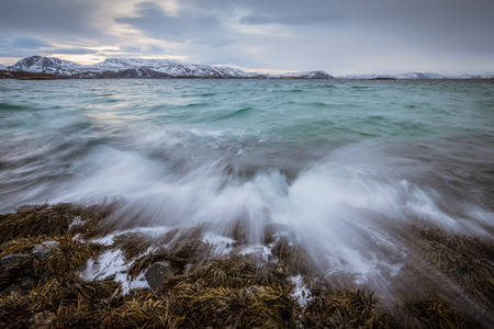 Pre-dawn photograph of  waves crashing on the rocks by the ocean in Sommaroy, Norway Standard-Bild