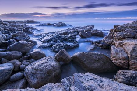 Pre-dawn Foto von nebligen Wellen auf den Felsen durch den South Coast in Südafrika