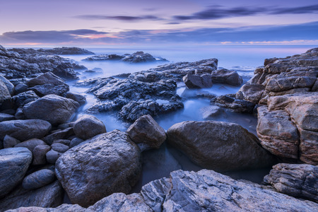 Pre-dawn photograph of misty waves crashing on the rocks by the South Coast in South Africa
