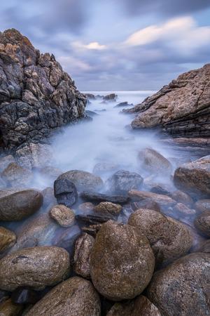 Sonnenuntergang Foto von nebligen Wellen auf den Felsen von der South Coast in Südafrika
