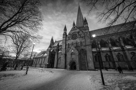 A wide angle black and white photograph of the Nidaros Cathedral in Norway, with a dramatic sky as the background. Standard-Bild