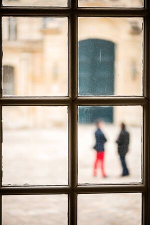An abstract photograph through a window at a museum, with two out of focus people standing outside, talking.