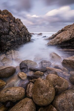 A vertical sunset landscape photograph of misty waves crashing on the rocks by the South Coast in South Africa