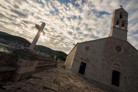 A diagonal shot of the sun rising through clouds with an old church and cross in the foreground, taken in Vis, Croatia.