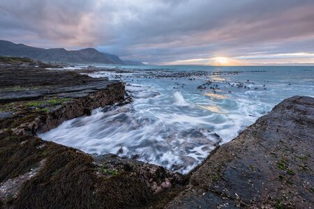 A beautiful early morning seascape photographed on a stormy day at sunrise in Hermanus, South Africa. Stockfoto