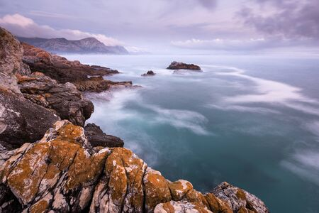 A beautiful golden early evening seascape photographed on a stormy day after sunset in Hermanus, South Africa.