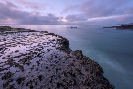 A beautiful early morning seascape with rocks in the foreground,  photographed on a stormy day before sunrise in Arniston, South Africa.