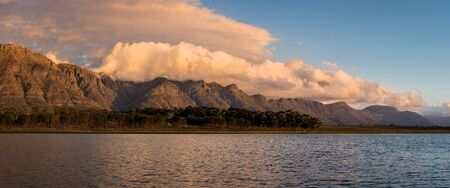 A panoramic landscape of a beautiful mountain range covered with clouds, with a lake in the foreground. This shot was taken in the Western Cape, South Africa. Standard-Bild