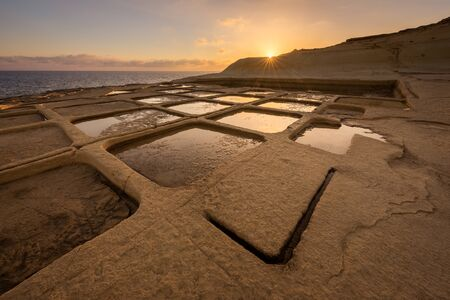 A beautiful golden sunrise photograph of the chequerboard of rock-cut salt pans protruding into the sea on the north coast of Gozo, Malta.