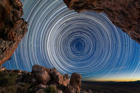 A beautiful night sky photograph with circular star trails framed by dramatic rocks in the foreground, taken in the Cederberg mountains in the Western Cape, South Africa. Standard-Bild