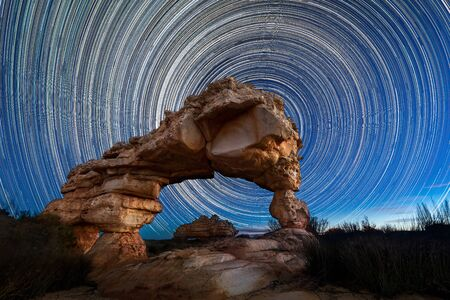 A beautiful night sky photograph with circular star trails behind a dramatic Rock Arch, taken in the Cederberg mountains in the Western Cape, South Africa.