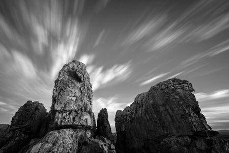 A stark black and white long exposure landscape with majestic rock formations in the foreground and fast moving clouds in the sky, taken in the Cederberg mountains in South Africa.