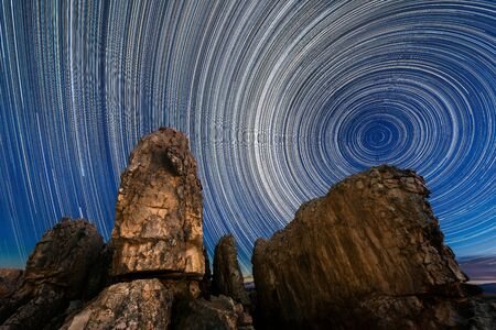 A beautiful night sky photograph with circular star trails against a deep blue sky with majestic dramatic rocks in the foreground, taken in the Cederberg mountains in the Western Cape, South Africa.
