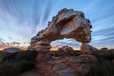 A dramatic landscape photograph of an incredible rock arch before sunrise, with fast moving clouds against a blue sky, taken in the Cederberg mountains, South Africa. Stock Photo