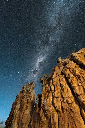 A beautiful vertical night sky landscape, with a yellow rock formation in the foreground and the Milky Way against a deep blue sky in the background, taken in the Cederberg mountains, South Africa.