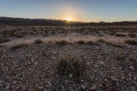 A textured rocky landscape at sunset, with the sun setting behind the mountains creating a golden sunburst, taken in the arid Richtersveld National Park, South Africa.