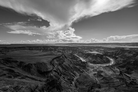 A black and white landscape taken at sunset on a stormy day on top of the arid and stark Fish River Canyon, Namibia, with the gorge and river in the foreground.