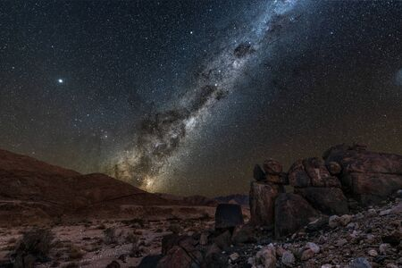 A beautiful night sky landscape with the Milky Way and galactic centre, and interesting rock formations in the foreground and mountains on the horizon, in the Richtersveld National Park, South Africa.