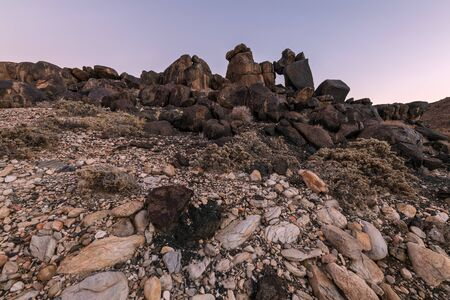 A textured rocky landscape after sunset with interesting rock formations in the foreground, taken in the Richtersveld National Park, South Africa.