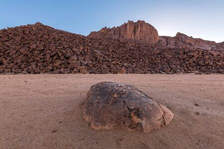 A beautiful arid mountain landscape at sunset, with fascinating geology and rock formations on the horizon and a large rock in the foreground, taken in the Richtersveld, South Africa.