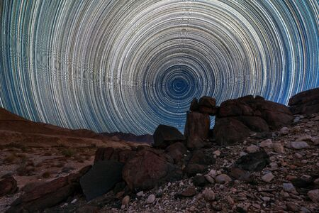 A beautiful night sky landscape with circular star trails, and interesting rock formations in the foreground and mountains on the horizon, in the Richtersveld National Park, South Africa.